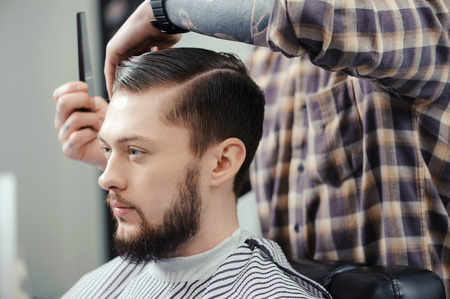 barber shop: Lumberjack style. Male barber in plaid shirt combing hair of a male client at barbershop