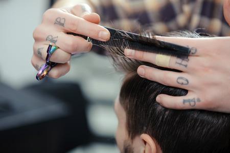 barbero: Barber�a. Primer plano de los barberos tatuado manos peinar el pelo hace corte de pelo a un cliente masculino Foto de archivo