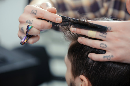 barber: Barbershop. Closeup of barbers tattooed hands combing hair making haircut to a male client Stock Photo