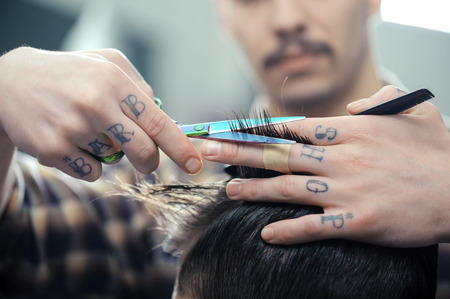 hairdressers: Barbershop. Closeup of barbers tattooed hands combing hair making haircut to a male client Stock Photo