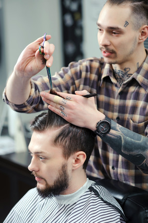 hairdressers shop: Barber profession. Young stylish tattooed barber cutting hair of a young bearded man at barbershop Stock Photo