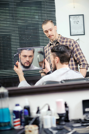 great job: Great job done. Young handsome bearded man looking precisely at his mirror reflection and evaluates barber job done