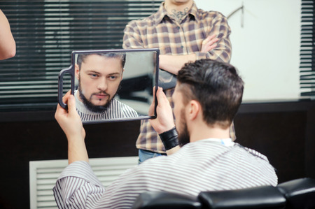 new look: New look. Close-up of a young bearded man looking to the small mirror with the reflection of a barber on the background in bigger mirror Stock Photo