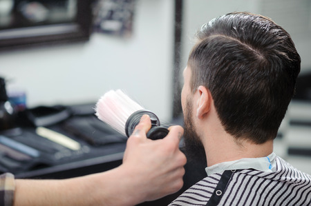 hairdressers shop: Hairstyling. Close-up of a barber touching with a brush haircut of a male client