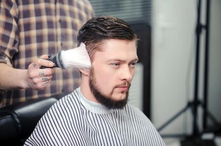 uomini belli: Hairstyling. Primo piano di un toccante barbiere con un taglio di capelli pennello di un cliente maschio