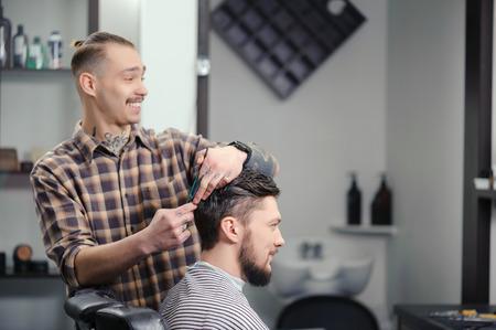 barbero: Conversación alegre. Alegre barbero hábil haciendo un corte de pelo con unas tijeras a un hombre barbudo joven