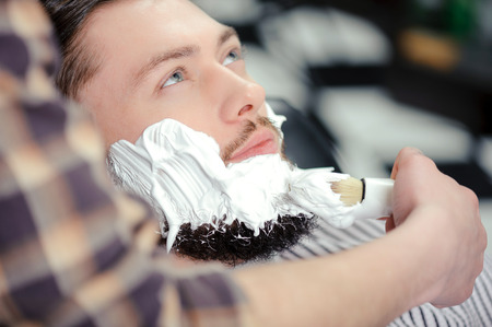 peluquero: Afeitarse la barba. Peluquer�a poner un poco de crema de afeitar en un cliente antes de afeitarse la barba en una peluquer�a Foto de archivo