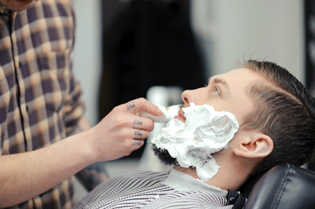 barber shave: Shaving the beard. Barber putting some shaving cream on a client before shaving his beard in a barber shop
