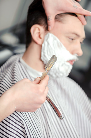 straight man: Skillful barber. Young man getting an old-fashioned shave with straight razor
