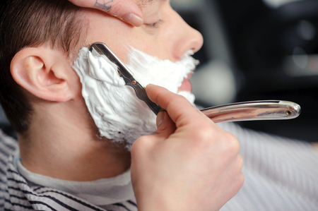 beau mec: Barbier adroit. Jeune homme d'obtenir un rasage � l'ancienne avec rasoir Banque d'images