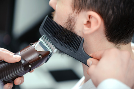 barber: Perfectly styled beard. Young bearded man getting shaved with hair clipper and a comb in a barber shop or hair salon Stock Photo