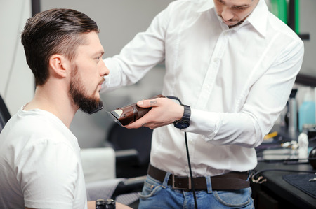 barber shop: Perfectly styled beard. Young bearded man getting shaved with hair clipper and a comb in a barber shop or hair salon Stock Photo