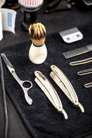 barber: Barber tools. Close-up of elegant old brush with white handle for shaving and range of old-fashioned straight razors on a barbers table Stock Photo