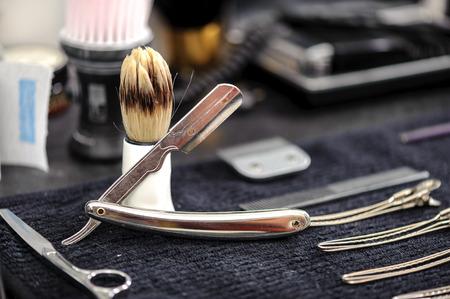 barbero: Herramientas del peluquero. Primer plano de elegante pincel viejo con mango blanco para el afeitado y la gama de anticuados navajas en una mesa de peluqueros