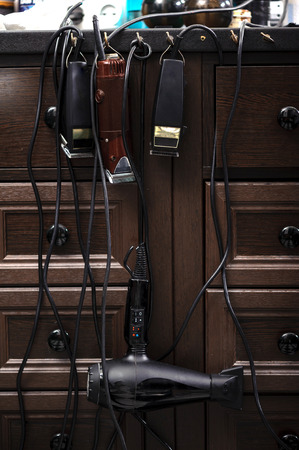hair clippers: Hairstyling accessories. Set of electric hair clippers and hairdryer hanged on a barbers table