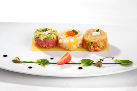 tuna fish: Mediterranean food. Tartar with tuna fish, avocado, salmon and caviar decorated with strawberry and capers