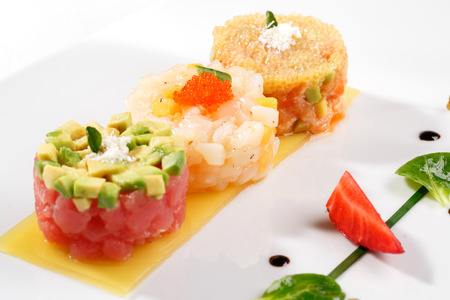 european cuisine: European cuisine. Tartar with tuna fish, avocado, salmon and caviar decorated with strawberry and capers