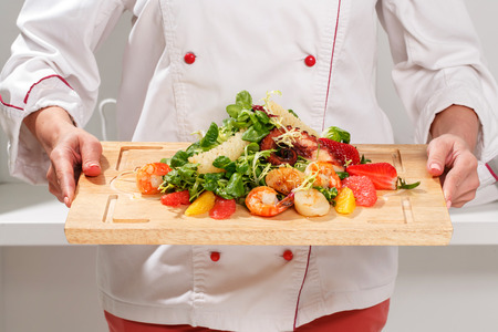 shrimp: Close-up of a cook holding a cutting board with salad with octopus, shrimps, scallops, strawberries, orange, mash-salad, frisee