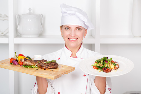 Smiling attractive female cook holding in one hand a cutting board with fried meat steak with vegetables grill and a plate with fresh octopus salad photo