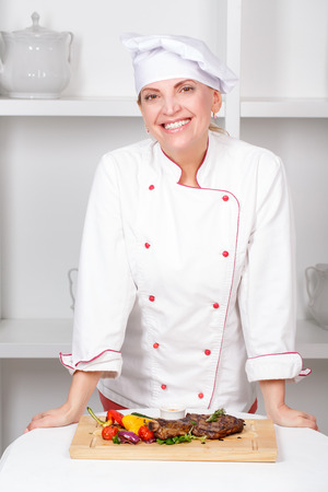 Cheerful female cook in uniform smiling into the camera leaning upon the table with the meat steak on it photo