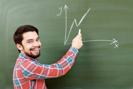 college life: College life. Young cheerful bearded student drawing a graph on a chalkboard and smiling at a camera Stock Photo