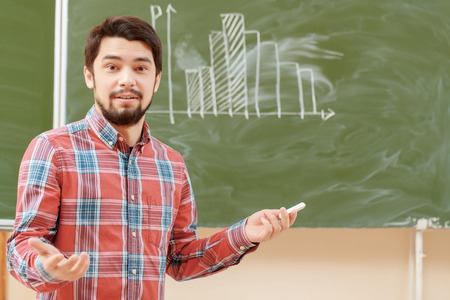 agitated: College classes. Young agitated male student standing on the background of a chalkboard with graph on it