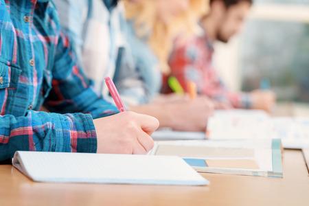 studium: Zkoušky. Oříznutí pohledu studentů psaní testu ve svých sešitů