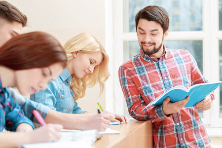 peer: Preparing for the exam. Young bearded student checking the answers of his female peer at college