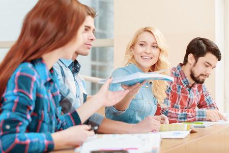students: Los estudiantes de aprendizaje. Los estudiantes que pasan el uno al otro libro de ejercicios sentado en el escritorio
