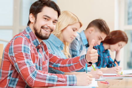 peers: Best time studying. Young smiling male student showing his thumb up sitting in class with his peers