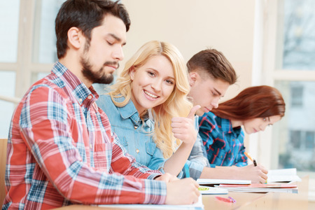 mates: Happy students. Young smiling blond female student showing thumb up sitting with her group mates at the desk