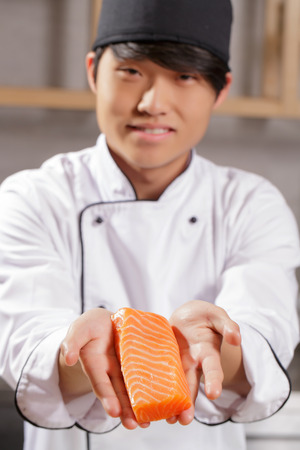 cook out: Only freshest fish. Young smiling Japanese cook stretching out to the camera piece of salmon with selective focus on fish Stock Photo