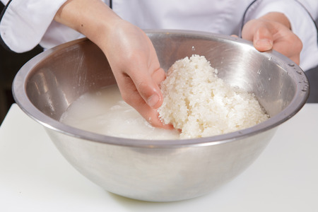 rice: Obtener el arroz limpio. Primer plano de las manos de un cocinero de lavar a fondo el arroz en un recipiente de acero Foto de archivo