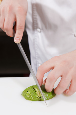 skillfully: Cooking craft. Close-up on hands of a cook skillfully slicing an avocado Stock Photo