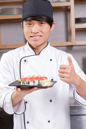 asian cook: Very tasty and fresh. Young smiling Asian cook showing his thumb up and holding a plate with tuna sushi rolls