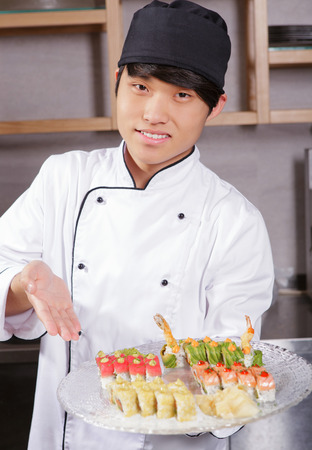 sushi set: Proud cook. Confident young Asian sushi cook points with hand on a plate with sushi set Stock Photo