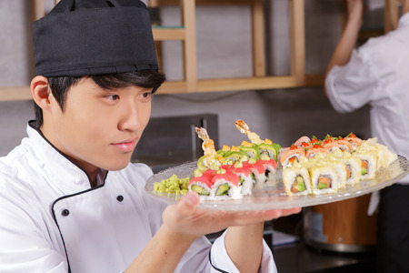 asian cook: Professional sushi cook. Young Asian cook looking precisely on a plate with various kinds of Japanese rolls Stock Photo