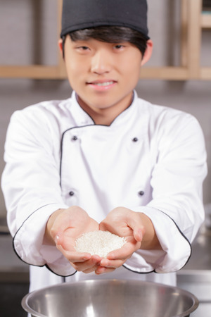 cook out: Healthy and tasty rice. Young smiling Japanese cook stretching out handful of rice in selective focus
