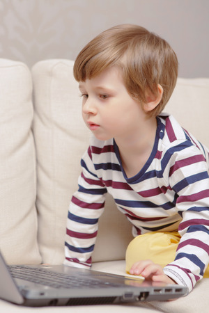 learner: Young learner. Close-up of a small boy using laptop at home Stock Photo