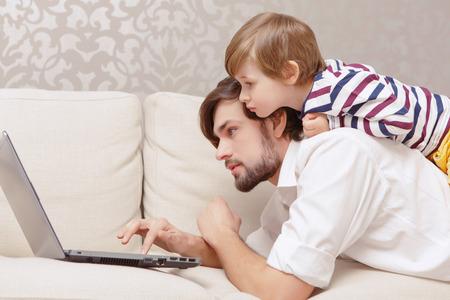 bel homme: Passer du temps ensemble. Photo verticale d'un jeune père beau et mignon utilisant un ordinateur portable sur un canapé à la maison