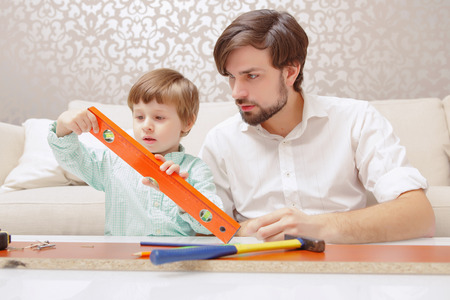 fingers put together: Small architect. Young handsome man and his son playing together with a building constructor and toy level