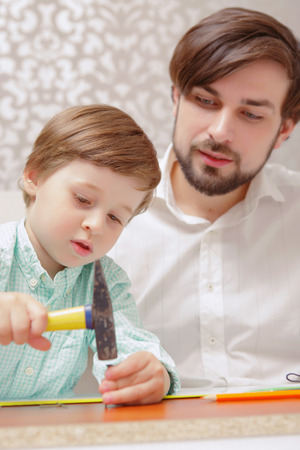 fingers put together: Constructing toys. Vertical shot of a boy holding a hammer together with his father