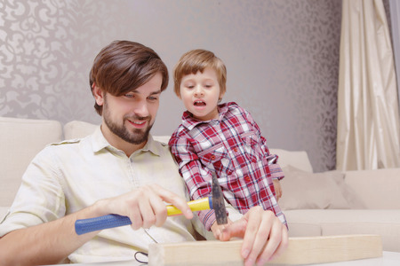 fingers put together: Men power. Young joyful father and curious son applying a hammer in toy constructor Stock Photo