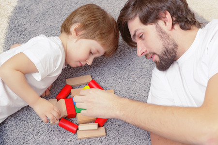 fingers put together: Family interaction. Young handsome father and cute son play building kit lying on a carpet in children room Stock Photo