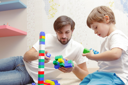 fingers put together: Fatherhood. Portrait of a small boy assembling with his father building kit