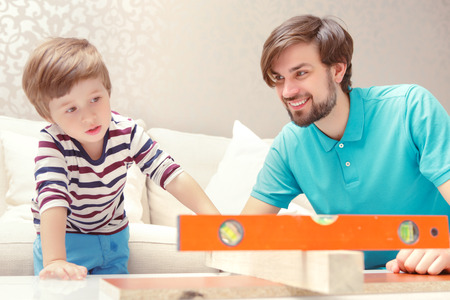 fingers put together: Straight and flat. Small boy applying a level playing with a wooden building kit with his father