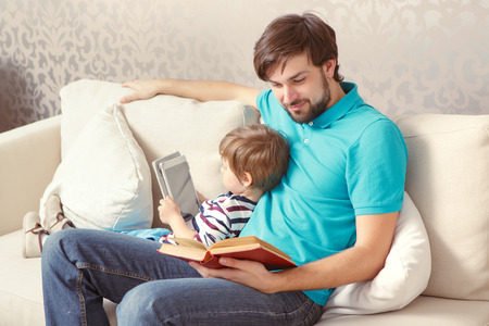 Different generations. Young father reading a book while his lovely son using a tablet device sitting at the home couch Stock Photo
