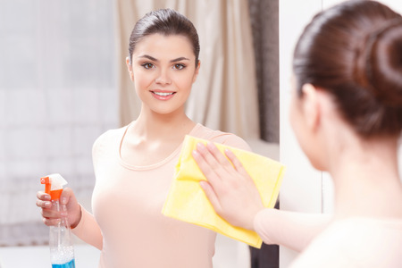 pureness: Pureness of reflection. Young lady standing in front of mirror and wiping it with help of yellow cloth and special mean of cleaning Stock Photo