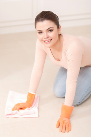 floor cloth: Cleaning sport. Young pretty lady washes floor on her knees with help of white cloth and orange rubber gloves