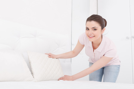 purely: On right place. Pretty young female is putting white pillow on purely white bed next to another one on white background of bedroom Stock Photo